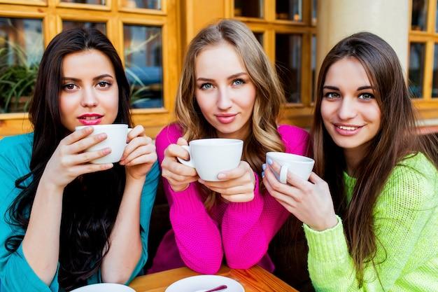 Schließen sie herauf lebensstilporträt von drei schönen jungen frauen, die im kaffee sitzen und heißen abschlag genießen. tragen sie leuchtend neongelben, rosa und blauen stilvollen pullover. festtage, essen und tourismuskonzept.