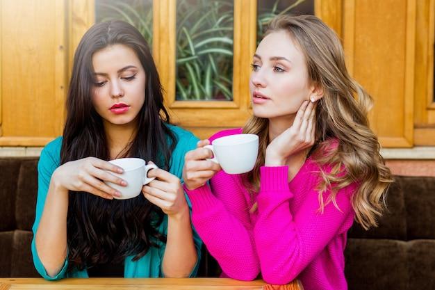 Schließen sie herauf lebensstilporträt von zwei schönen jungen freunden, die im café sitzen und heißes t-stück genießen. tragen von leuchtendem neongelb und rosa stilvollem pullover. festtage, essen und tourismuskonzept.