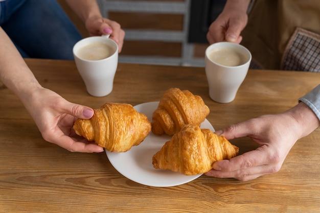 Schließen sie herauf leute, die croissants und kaffee halten