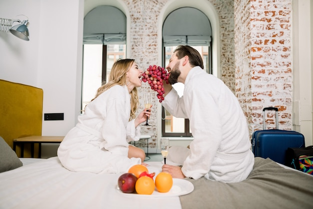 Schließen sie herauf lustiges porträt des paares in den bademänteln auf dem bett, das frühstück zusammen genießt, frische traube isst und lacht.