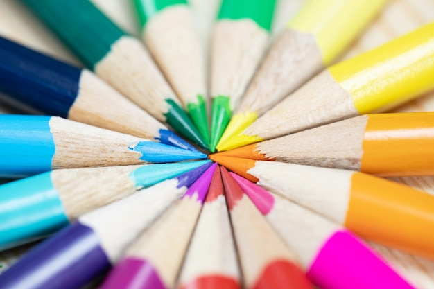 Schließen sie herauf makroaufnahme von farbstiften stapel bleistiftspitzenfedern diagonal in einem kreis auf dem schreibtisch aus holz. ideenbildung zurück in die schule. Premium Fotos