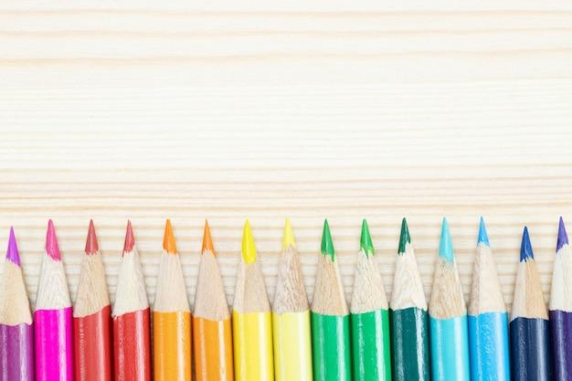 Schließen sie herauf makroaufnahme von farbstiften stapel bleistiftspitzenfedern diagonal in einem kreis auf dem schreibtisch aus holz. ideenbildung zurück in die schule.