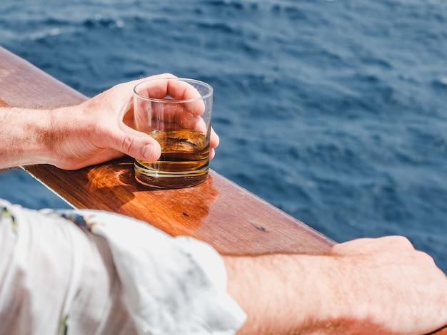 Schließen sie herauf mann, der ein glas whisky hält