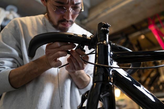 Schließen sie herauf mann, der fahrrad repariert
