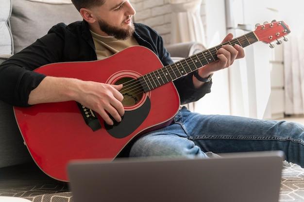 Schließen sie herauf mann, der gitarre auf boden spielt