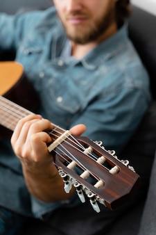 Schließen sie herauf mann, der gitarre zu hause spielt