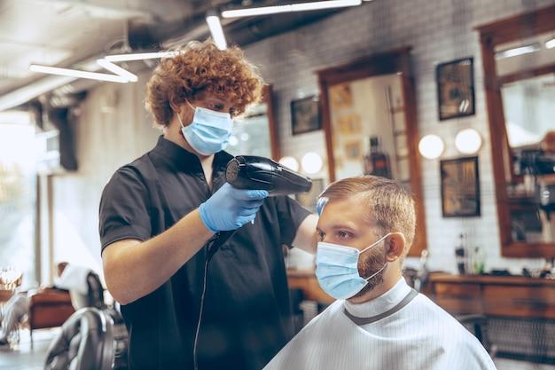 Schließen sie herauf mann, der haarfriseur am friseursalon trägt maske während coronavirus-pandemie schneidet.