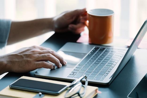 Schließen sie herauf mann, der intelligenten laptop zu hause verwendet