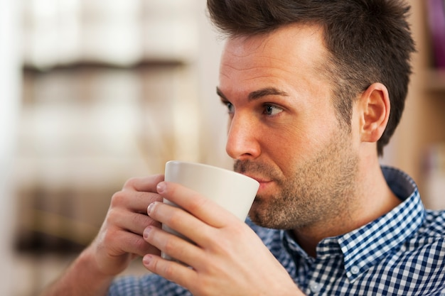 Schließen sie herauf mann, der kaffee nach hause trinkt