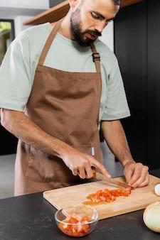 Schließen sie herauf mann, der tomate schneidet