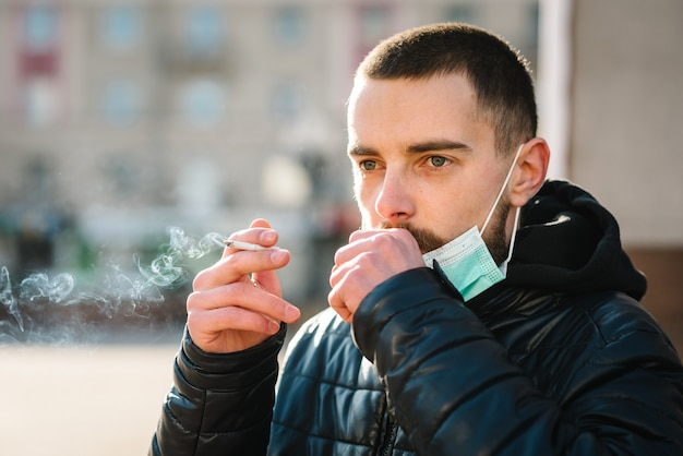 Schließen sie herauf mann mit maske während der covid-19-pandemie, die hustet und eine zigarette auf der straße raucht.