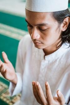 Schließen sie herauf mann muslim, der gebet in der moschee tut