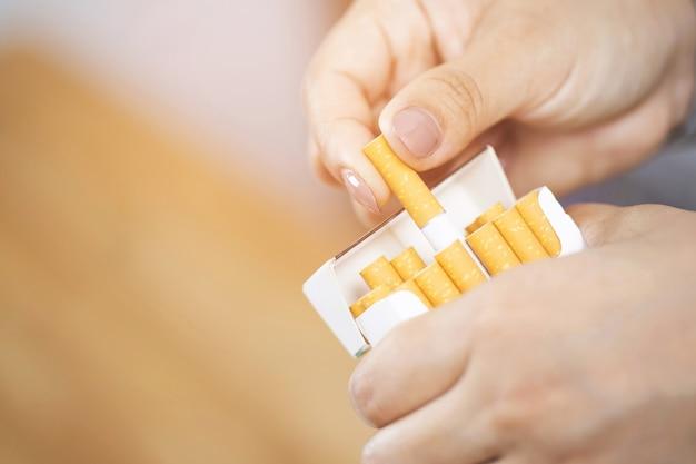 Schließen sie herauf mannhandhalten, schälen sie es von der zigarettenschachtel, bereiten sie das rauchen einer zigarette vor. packaufstellung.