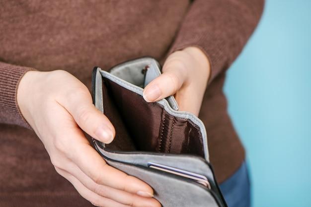 Schließen sie herauf mannperson, die eine leere brieftasche in den händen eines hält. mann kein geld. kein geld, um den einkauf zu bezahlen, zu verkaufen oder zu bezahlen.