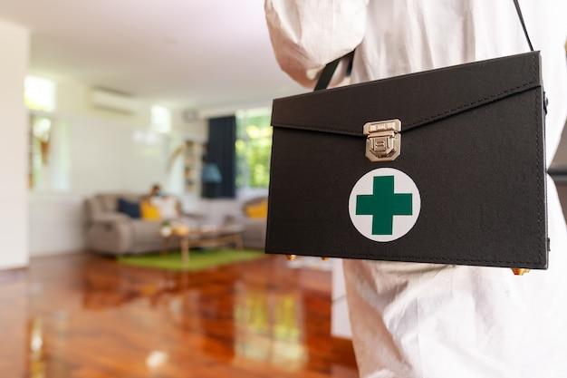 Schließen sie herauf medizinisches personal im psa-anzug der persönlichen schutzausrüstung mit hintergrund der asiatischen frau mit gesichtsmaske lieferung coronavirus covid test zu hause konzept