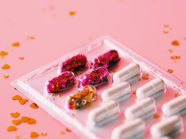Schließen sie herauf medizinkapseln über rosa hintergrund, kopienraum.