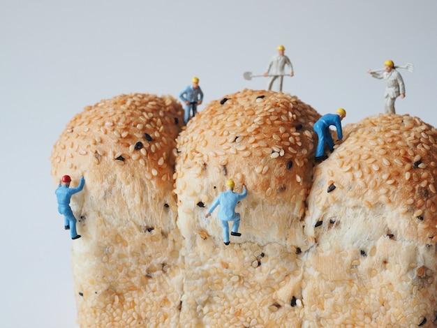 Schließen sie herauf miniaturleute viele des arbeitskraftmannes, der an ganzem kornbrothintergrund arbeitet