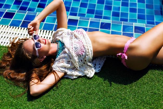 Schließen sie herauf mode-sommerporträt der atemberaubenden schönen frau, die in der nähe des pools liegt, entspannen sie sich und nehmen sie ein sonnenbad. trendige accessoires und schmuck, luxuriöser urlaubsstil, getönte leuchtende farben.