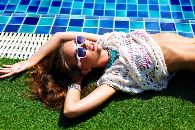Schließen sie herauf mode-sommerporträt der atemberaubenden schönen frau, die in der nähe des pools liegt, entspannen sie sich und nehmen sie ein sonnenbad.