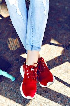 Schließen sie herauf modebild der frauenfüße, tragende vintage-jeans und stilvolle rote turnschuhe, helle getönte farben.