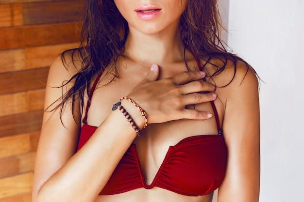 Schließen sie herauf modebild der jungen frau im trendigen bikini mit nassen haaren und großen vollen lippen, die ihr hotelzimmer in innenräumen posieren.