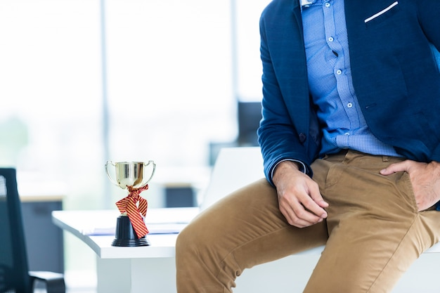 Schließen sie herauf modebild des handgelenks in einem geschäftsanzug des manndetails eines geschäftsmannes, der hand des mannes in der braunen oder goldenen hosentasche und im tragen der blauen jacke eine championschale auf dem tisch im büroraum.