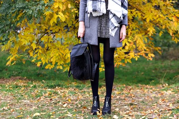 Schließen sie herauf modedetails, frau, die im stadtherbstpark der stadt, straßenartblick, trendige lederstiefel, rucksack, luxuskleid und -mantel, helle farben aufwirft.
