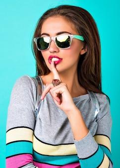 Schließen sie herauf modeporträt der eleganten hübschen frau, des sexy gesichtes, des hellen schminkens, des stilvollen lässigen pullovers, der frühlingspastellfarben, setzen sie finger zu ihrem mund.