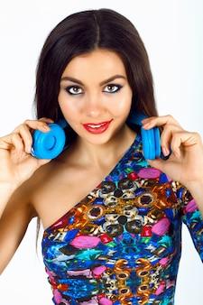 Schließen sie herauf modeporträt der herrlichen jungen frau mit hellem sexy make-up, das helles oberteil und große blaue dj-kopfhörer trägt.