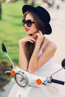 Schließen sie herauf modeporträt der jungen blonden frau im weißen tüllrock und in den schwarzen absätzen, die auf vintage roller sitzen.