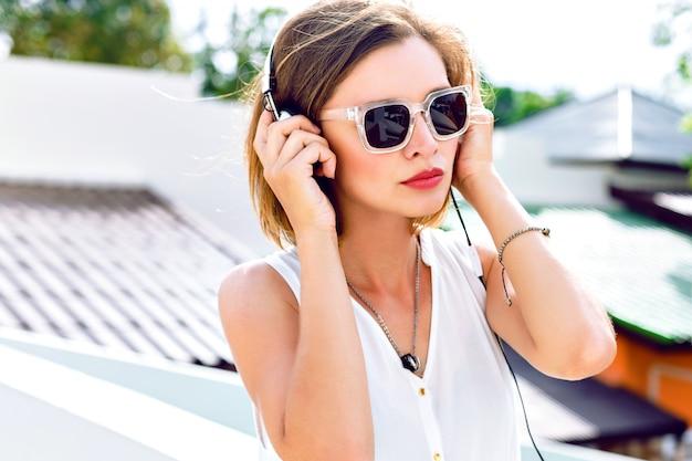 Schließen sie herauf modeporträt der jungen sexy frau, die ihre lieblingsmusik in ihren kopfhörern, hellem make-up, frischen sommerfarben hört. auf dem dach posieren, positive stimmung.