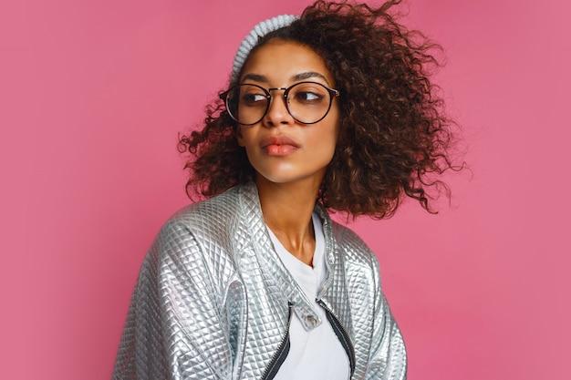 Schließen sie herauf modeporträt der mischrassenfrau mit brauner haut und lockiger afrikanischer frisur auf lebendigem rosa hintergrund. trägt eine silberne winterjacke und einen grauen hut.