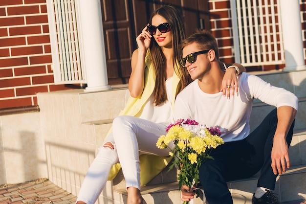 Schließen sie herauf modeporträt des jungen stilvollen fröhlichen paares in der liebe, die draußen auf der straße aufwirft, lächelt, lacht, umarmt und zeit zusammen genießt. helle warme sonnige farben. romantische stimmung.