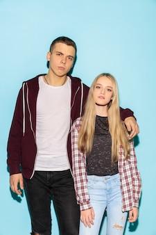 Schließen sie herauf modeporträt von zwei jungen coolen hipster-mädchen und jungen, die jeans tragen.