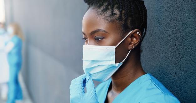 Schließen sie herauf müde junge afroamerikanische ärztin, die medizinische maske abnimmt und heißes getränk nippt, während sie sich ausruhen und an wand im freien lehnen. hübsche krankenschwester, die kaffee trinkt und sich nach harter arbeit ausruht