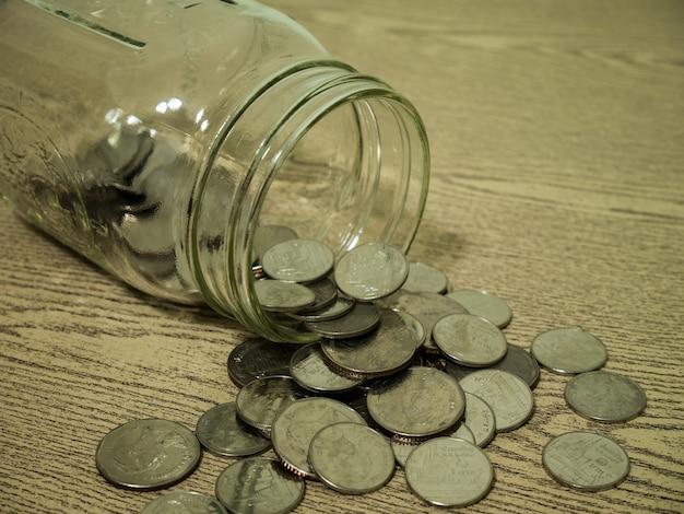 Schließen sie herauf münzen und glaslüge auf holztisch