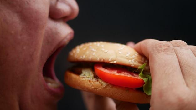 Schließen sie herauf mundöffnung für hamburger essen