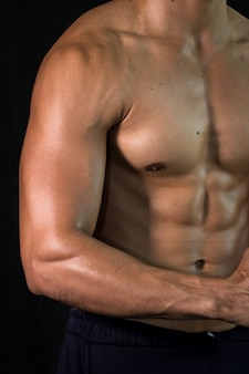 Schließen sie herauf muskulösen schönen körper des bodybuilders auf schwarzem hintergrund