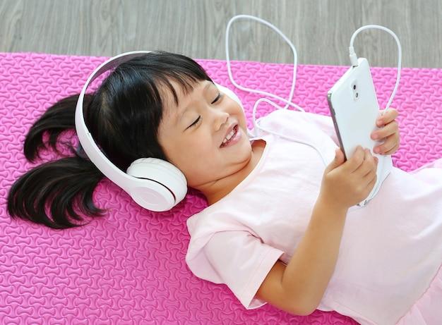 Schließen sie herauf nette hörende musik des kleinen mädchens mit kopfhörern und smartphone