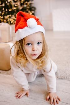 Schließen sie herauf nettes kleines mädchen in einer roten weihnachtsmannmütze mit weihnachtsgeschenken, die die kamera betrachten.