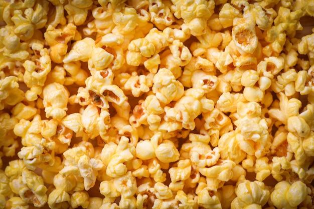 Schließen sie herauf popcorn - draufsicht des süßen butterpopcornbeschaffenheitshintergrundes