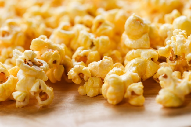 Schließen sie herauf popcorn- / süßes butterpopcornsalz auf hölzernem backgroubd