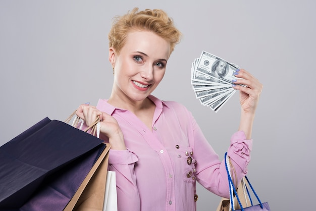 Schließen sie herauf porträt auf junge frau, die einkaufstaschen und geld hält