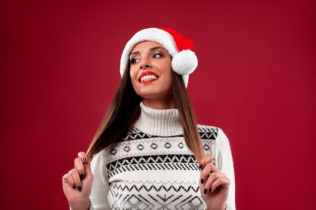 Schließen sie herauf porträt beautifiul kaukasische frau in rotem sankt-hut auf roter wand. weihnachten neujahrskonzept. lächelnde positive gefühle der netten frauenzähne berührt haar mit freiem exemplarplatz