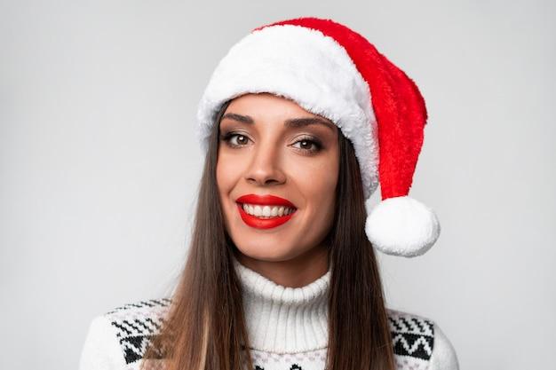 Schließen sie herauf porträt beautifiul kaukasische frau in rotem sankt-hut auf weißer wand. weihnachten neujahrskonzept. lächelnde positive gefühle der netten frauenzähne mit freiem exemplarplatz