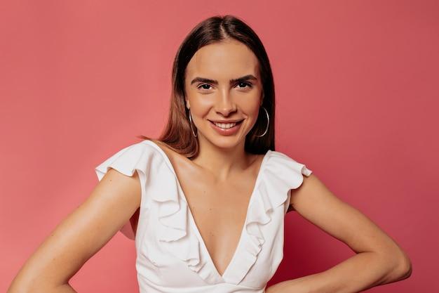 Schließen sie herauf porträt der attraktiven glücklichen frau in der weißen spitze, die über rosa wand mit glücklichem lächeln aufwirft