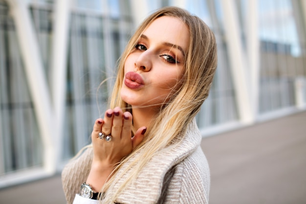 Schließen sie herauf porträt der eleganten blonden frau, die auf der straße tragenden mantel, natürliches make-up, sinnliches gesicht und lange blonde haare, windiges herbstwetter aufwirft.