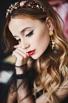 Schließen sie herauf porträt der eleganten luxuriösen frau mit perfektem make-up und teurem trendigem goldschmuck. modell mädchen mit gewellter frisur, hellem make-up und sexy roten lippen. luxusleben. luxuriöse mode