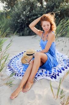 Schließen sie herauf porträt der erstaunlichen lächelnden rothaarigen frau im blauen kleid, das am sonnigen strand des frühlings auf handtuch entspannt. strohhut, stilvolle armbänder und halskette.
