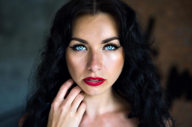 Schließen sie herauf porträt der erstaunlichen schönheitsfrau mit flauschigen brünetten haaren und großem blauen ja, das gerade schaut, weiße uhr und helles make-up tragend.